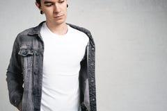Giovane tipo bello che porta maglietta e rivestimento in bianco fotografia stock