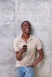 Giovane tipo bello che ride con il telefono cellulare Immagine Stock