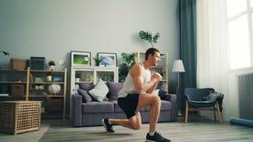 Giovane tipo bello che si esercita a casa facendo gli esercizi di sport per le gambe ed il corpo archivi video