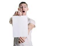 Giovane tipo bello con un foglio bianco di carta, osservante sorpreso la struttura Posto per la firma, testo Struttura orizzontal Fotografia Stock Libera da Diritti