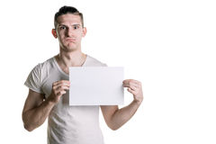 Giovane tipo bello con un foglio bianco di carta, osservante sorpreso la struttura Posto per la firma, testo Struttura orizzontal Immagini Stock