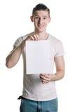 Giovane tipo bello con un foglio bianco di carta, sembrante colpo sorpreso Posto per la firma, testo Struttura verticale Immagine Stock