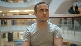 Giovane tipo bello in maglietta grigia che si siede in caffè del centro commerciale Concetto di consumismo di acquisto stock footage