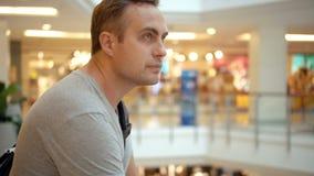 Giovane tipo bello in maglietta grigia che sta nel centro commerciale Concetto di consumismo di acquisto archivi video