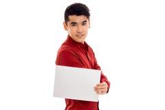 Giovane tipo bello in maglietta rossa con il cartello vuoto che esamina la macchina fotografica isolata su fondo bianco Fotografia Stock Libera da Diritti