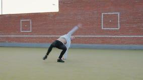 Giovane tipo caucasico sveglio in pantaloni neri del denim e maglione bianco che ballano una serie di movimenti spettacolari con video d archivio