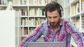 Giovane tipo che ascolta la musica sulle cuffie sul computer portatile archivi video