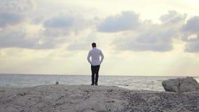 Giovane tipo che cammina sulla spiaggia e che gode stupendo vista della spiaggia cyprus Pafo archivi video