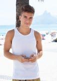 Giovane tipo che compone con il telefono alla spiaggia Fotografie Stock