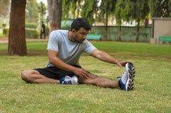 Giovane tipo che fa allungando esercizio in un parco Fotografia Stock Libera da Diritti