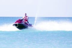 Giovane tipo che gira su un jet ski Immagini Stock