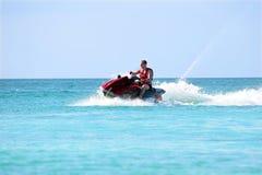 Giovane tipo che gira su un jet ski sul mare caraibico Immagini Stock Libere da Diritti