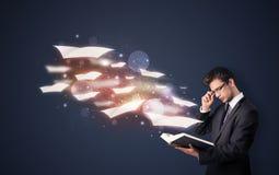 Giovane tipo che legge un libro con gli strati di volo che escono dalla BO Fotografie Stock