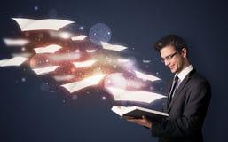 Giovane tipo che legge un libro con gli strati di volo che escono dalla BO Immagine Stock