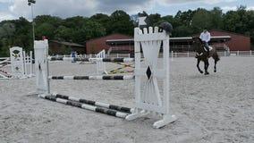 Giovane tipo che salta sopra la barriera al a cavallo video d archivio