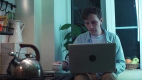 Giovane tipo che scrive sul computer che si siede alla cucina mentre bollitore che bolle sulla stufa video d archivio