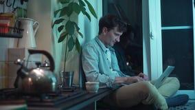 Giovane tipo che scrive sul computer che si siede alla cucina mentre bollitore che bolle sulla stufa stock footage