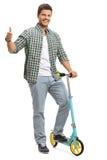 Giovane tipo con un motorino che fa un pollice sul gesto Fotografia Stock