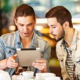 Giovane tipo dei pantaloni a vita bassa che si siede in un coffe di chiacchierata e bevente del caffè Immagini Stock