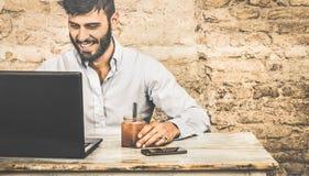 Giovane tipo dei pantaloni a vita bassa con i baffi facendo uso del computer portatile Fotografia Stock Libera da Diritti