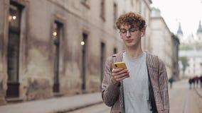 Giovane tipo dei pantaloni a vita bassa con i vetri che chiacchiera con gli amici alle reti sociali ed ascoltare musica, facendo  video d archivio