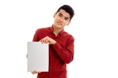 Giovane tipo di eleganza in maglietta rossa con il cartello vuoto che esamina la macchina fotografica isolata su fondo bianco Fotografie Stock