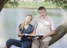Giovane tipo e la ragazza con i manuali sulla banca del lago Fotografie Stock