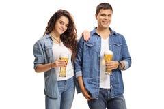 Giovane tipo e una ragazza che tiene i vetri di birra immagini stock