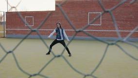 Giovane tipo energetico, un ballerino della via in pantaloni neri e un maglione bianco, realizzante i bei movimenti sul archivi video