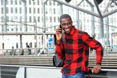 Giovane tipo felice alla stazione ferroviaria facendo uso del telefono cellulare Fotografia Stock Libera da Diritti