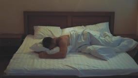 Giovane tipo a letto che copre la sue testa ed orecchie di cuscino poichè non vuole svegliare, soffrente dall'allarme rumoroso de stock footage