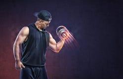 Giovane tipo muscolare che solleva una testa di legno a preparare il suo bicipite Fotografia Stock Libera da Diritti