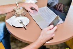 Giovane tipo nel funzionamento del caffè dietro il computer portatile immagini stock