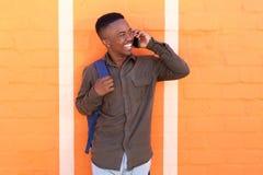 Giovane tipo nero felice che parla sul pone mobile dalla parete arancio Immagine Stock