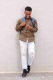Giovane tipo nero felice che sorride con il cellulare e la borsa Fotografia Stock Libera da Diritti