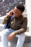 Giovane tipo nero fresco che ride e che parla sul telefono cellulare Immagini Stock