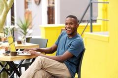 Giovane tipo nero sorridente che si siede ad un caffè con un computer portatile Immagine Stock Libera da Diritti