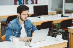 Giovane tipo serio con la barba che lavora al computer portatile fotografie stock