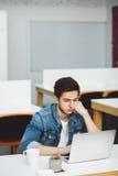 Giovane tipo serio con la barba che lavora al computer portatile Fotografie Stock Libere da Diritti