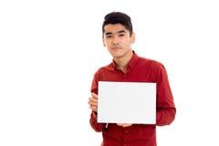 Giovane tipo serio in maglietta rossa con il cartello vuoto che esamina la macchina fotografica isolata su fondo bianco Immagine Stock Libera da Diritti