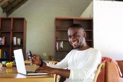 Giovane tipo sorridente che si siede alla tavola con il telefono cellulare ed il computer portatile Immagini Stock