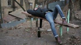 Giovane tipo ubriaco che si trova sul banco, problema di abuso di alcool, postumi di una sbornia dopo il partito video d archivio