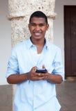 Giovane tipo in un messaggio di battitura a macchina della camicia blu al telefono Fotografie Stock Libere da Diritti
