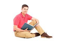 Giovane tirante bello che si siede su un pavimento e che legge un libro Fotografia Stock