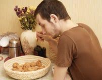 Giovane tirante con tè e fetta biscottata nella cucina Fotografie Stock Libere da Diritti