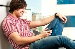 Giovane tirante d'avanguardia che digita un messaggio Immagine Stock