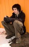 Giovane triste con i telefoni capi Fotografie Stock Libere da Diritti