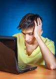 Giovane triste con il computer portatile Fotografie Stock Libere da Diritti