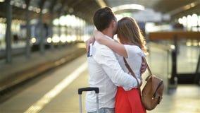 Giovane triste nell'amore che accarezza e che dice arrivederci alla sua amica nella stazione ferroviaria prima della partenza su  archivi video