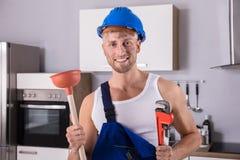 Giovane tuffatore di Holding Wrench And dell'idraulico in cucina fotografie stock libere da diritti